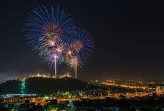 Fuoco d'artificio sopra la montagna fra la città Immagine Stock
