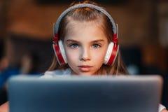 Fuoco della bambina in cuffie facendo uso del computer portatile Fotografia Stock