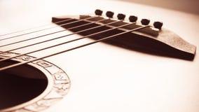 Fuoco della chitarra acustica sul ponte e sulle corde fotografia stock