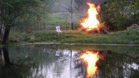Fuoco della primavera vicino allo stagno e sedia bianca su erba stock footage