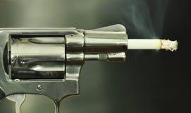 Fuoco della sigaretta nelle uccisioni di fumo confrontate della latta della museruola di pistola Immagini Stock Libere da Diritti