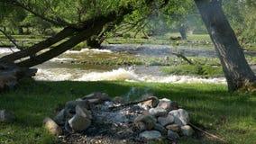 Fuoco di accampamento sul fiume della montagna stock footage