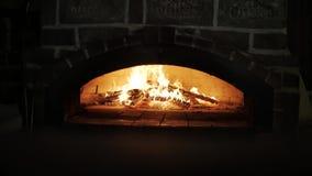 Fuoco in forno di pietra infornato di legno Alimenti a rapida preparazione cucinati in un forno legno-infornato video d archivio