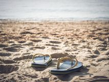 Fuoco molle alle paia dei flip-flop sulla spiaggia di sabbia bianca immagini stock
