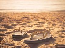 Fuoco molle alle paia dei flip-flop sulla spiaggia di sabbia bianca fotografia stock libera da diritti