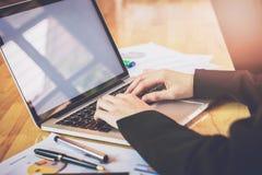 Fuoco molle del computer portatile funzionante della mano della donna sullo scrittorio di legno in ufficio alla luce di mattina Immagini Stock