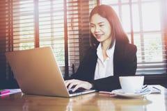 Fuoco molle del computer portatile funzionante della mano della donna sullo scrittorio di legno in ufficio alla luce di mattina E Fotografia Stock Libera da Diritti