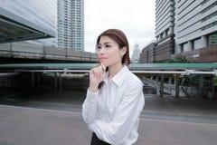 Fuoco molle di giovane donna di affari asiatica sicura che sta e che guarda lontano nei precedenti della città Concetto della don Fotografia Stock