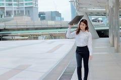 Fuoco molle di giovane donna asiatica attraente di affari che cammina e che esamina lontano il marciapiede del fondo urbano della Fotografia Stock Libera da Diritti