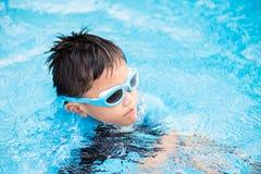 Fuoco molle sul giovane bambino asiatico felice con gli occhiali di protezione di nuotata immagini stock libere da diritti
