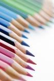Fuoco ondulato colorato delle matite su rosso Fotografia Stock Libera da Diritti