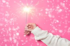 Fuoco scintillante del Bengala in una mano del ` s della donna su un fondo rosa Concetto di Natale Fotografia Stock Libera da Diritti