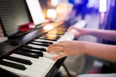 Fuoco selettivo alla mano del bambino che gioca piano in scena fotografia stock