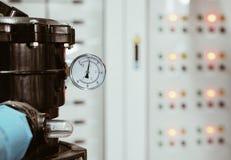 Fuoco selettivo alla misura del portone e della valvola di grandi pompa idraulica/fondo con luce del pannello elettrico fotografia stock