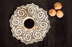 Fuoco selettivo con il vassoio, le noci e la tazza di caffè in bianco e nero della cucina Fotografie Stock