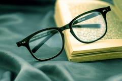 Fuoco selettivo degli occhiali della lettura con il libro aperto Fotografia Stock Libera da Diritti