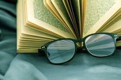 Fuoco selettivo degli occhiali della lettura con il libro aperto Fotografie Stock