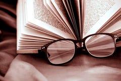 Fuoco selettivo degli occhiali della lettura con il libro aperto Immagini Stock