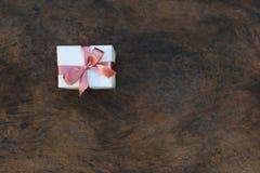 Fuoco selettivo del contenitore di regalo giallo con il nastro rosa su vecchio woode immagine stock libera da diritti