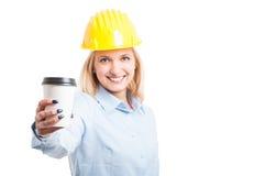 Fuoco selettivo dell'ingegnere della donna che mostra caffè per andare tazza immagini stock libere da diritti