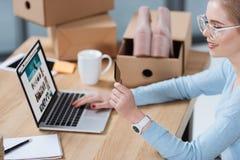 fuoco selettivo della donna con la carta di credito a disposizione che esamina lo schermo del computer portatile fotografia stock libera da diritti