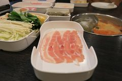Fuoco selettivo di carne di maiale affettata fresca cruda con le verdure per lo shabu di shabu o di cottura e il sukiyaki, alimen immagini stock libere da diritti