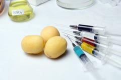Fuoco selettivo di frutta con attrezzatura medica e le siringhe colorate con gli antiparassitari su un fondo bianco fotografia stock