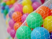 Fuoco selettivo di molte palle di plastica variopinte nelle reti nei colori differenti fotografie stock