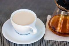 Fuoco selettivo di tè al latte nero in tazza bianca della porcellana con la teiera accanto su una tavola metallica immagini stock