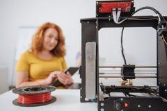 Fuoco selettivo di un filamento che si trova vicino alla stampante 3d Immagine Stock