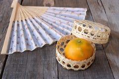 Fuoco selettivo sull'arancia in un canestro sul bordo di legno anziano con il fondo cinese del ventaglio concetto cinese felice d Fotografia Stock Libera da Diritti