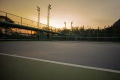 Fuoco selettivo sulla linea di base del campo da tennis con il fondo del cielo di tramonto Paesaggio del posto di sport fotografia stock libera da diritti
