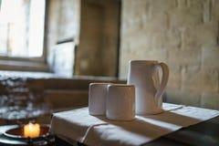 Fuoco selettivo sulla teiera e sulle tazze di tè ceramiche bianche con luce Fotografie Stock Libere da Diritti