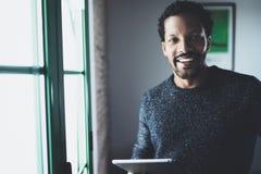 Fuoco selettivo Uomo africano barbuto sorridente che esamina macchina fotografica e che tiene compressa digitale disponibila vici Fotografia Stock