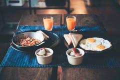 Fuoco selezionato, prima colazione sulla tavola di legno con il panino, uovo fritto ed arancia immagini stock libere da diritti