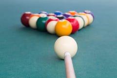 Fuoco sulla stecca che mira palla bianca per rompere i billards dello snooker fotografia stock