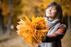 Fuoco sulle foglie gialle Donna castana nel parco di autunno con il cappotto e la sciarpa alla moda del plaid fotografie stock libere da diritti