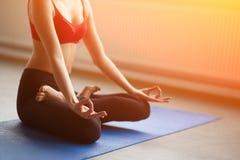 Fuoco sulle mani Chiuda sulla ragazza fanno l'yoga all'interno Immagine Stock