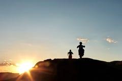Fuori dai motociclisti del motore della strada al tramonto fotografia stock libera da diritti