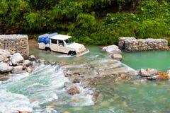 Fuori dai veicoli stradali con i turisti che attraversano un fiume nell'area di conservazione di Annapurna, il Nepal immagine stock libera da diritti