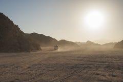 Fuori dal veicolo stradale che attraversa through il paesaggio arido del deserto Fotografia Stock Libera da Diritti