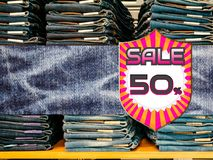 50% fuori sui jeans blu del denim nel fondo del negozio Fotografie Stock