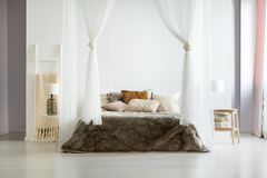 Fur bedding in comfy interior. Fur brown bedding and glass lamp in minimalist comfy bedroom with natural interior design and bed canopy Royalty Free Stock Photography