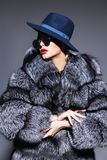 Fur coat and hat. Gorgeous blonde woman posing in luxurious fur coat and a hat. Fashion, beauty. Studio shot royalty free stock photos