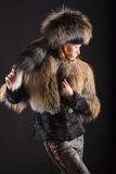 Fur in the dark. The young woman posing in fur coat on dark Royalty Free Stock Images