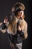 Fur in the dark. The young woman posing in fur coat on dark Stock Photos