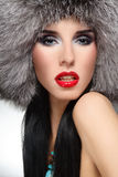 Fur fashion. Portrait of beautiful glamorous brunette in stylish fur hat royalty free stock photos