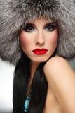 Fur fashion. Portrait of beautiful glamorous brunette in stylish fur hat Royalty Free Stock Images