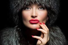 Fur Fashion. Beautiful Girl with red lips and manicure in Fur Ha Stock Images