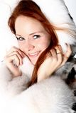 Fur girl. Happy red hair girl in fur Stock Image